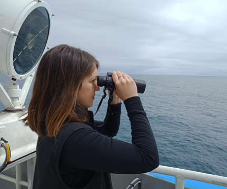 Cassie Layton with binoculars on the ship