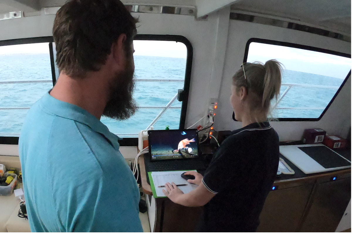 Researchers on a vessel review video recorded on the seafloor