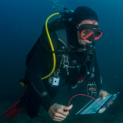 A volunteer SCUBA diver recording biodiversity for Reef Life Survey.