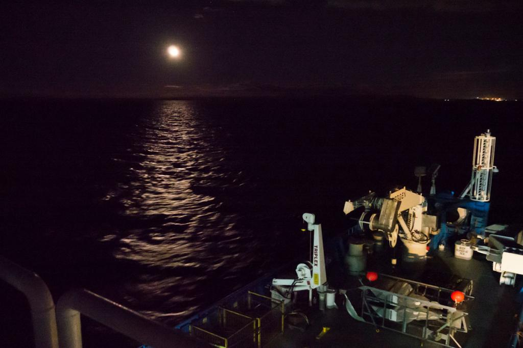 The RV Investigator heads out at night from Bell Bay Port.